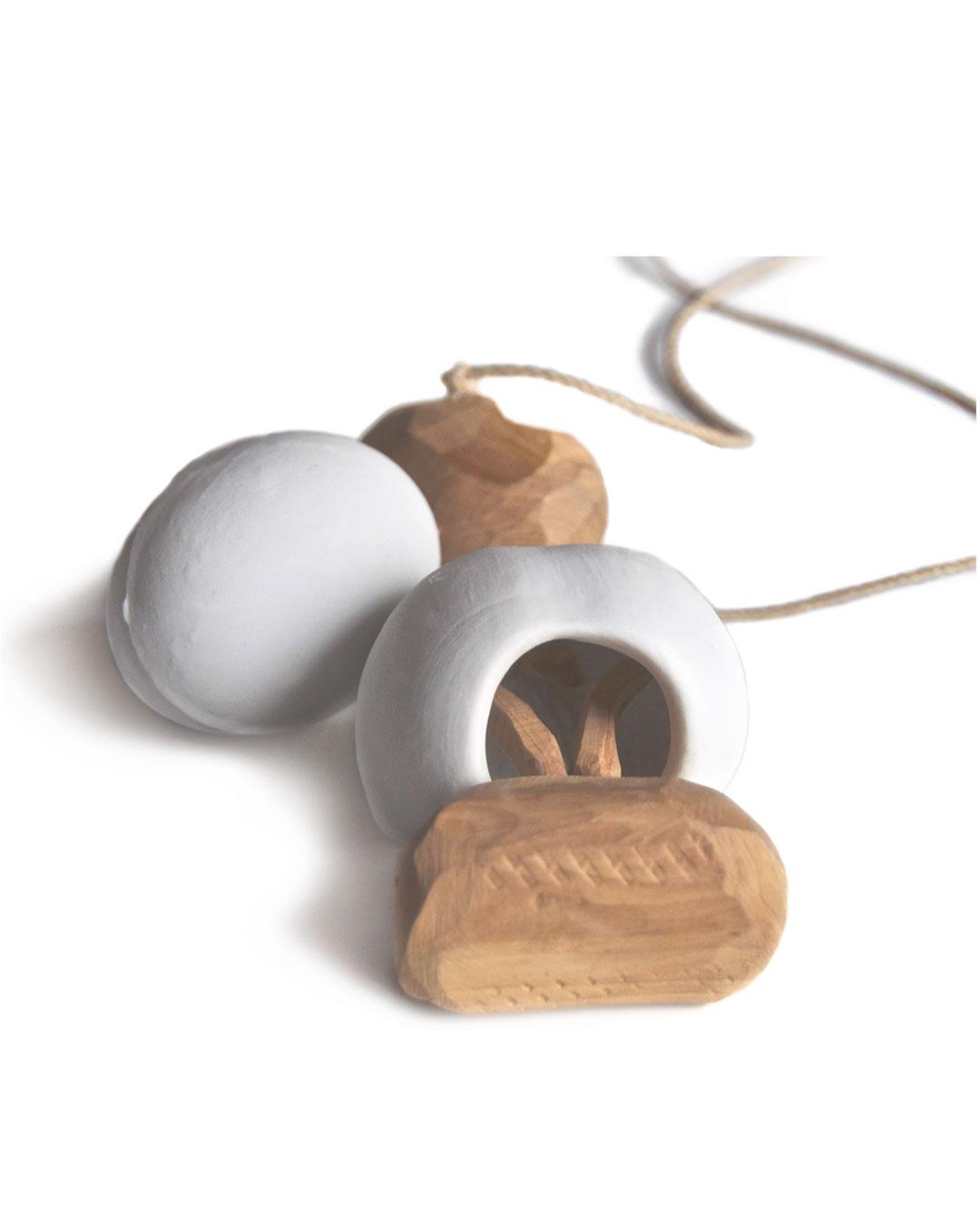Antje Bräuer, Assymmetrie, 1999, pendant; porcelain, wood, cord, 370 x 85 x 32 mm, €940